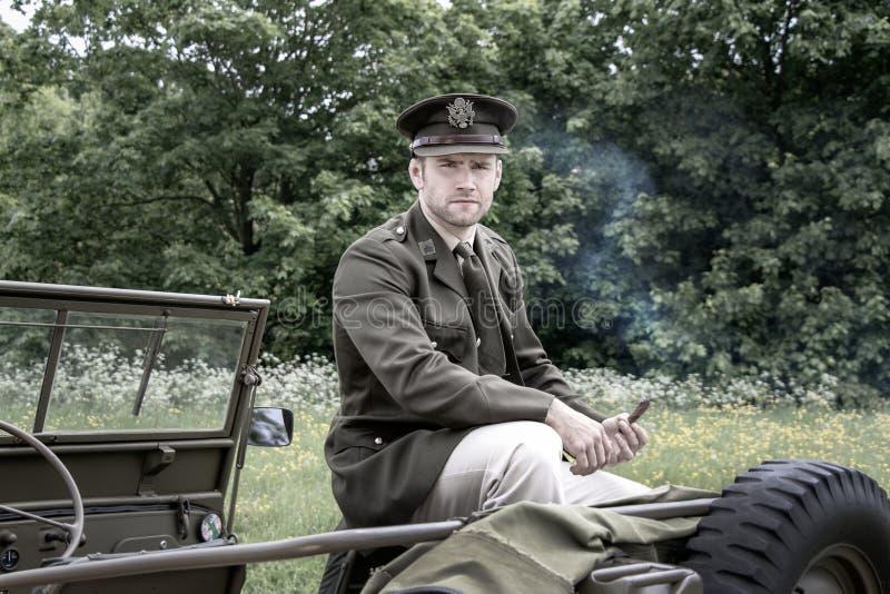 一致的抽烟的雪茄的英俊的美国人WWII美国兵陆军将校,当坐威廉吉普时 库存照片