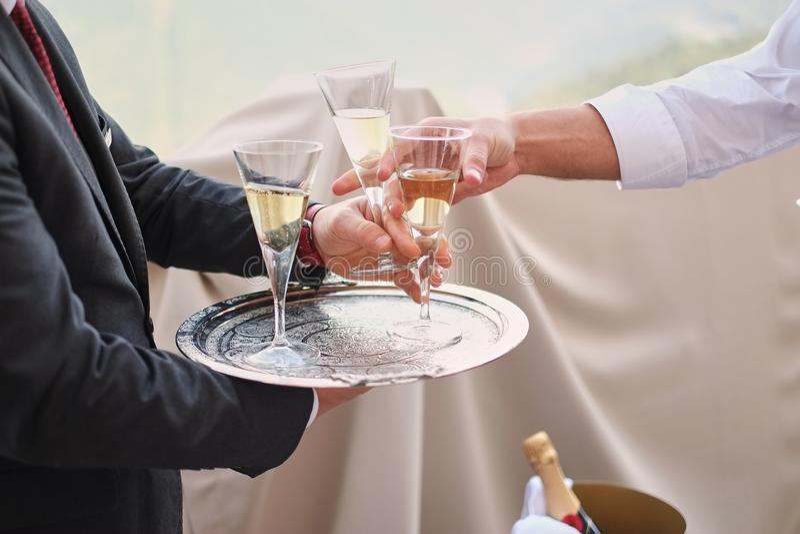 一致的服务香槟的专业男性侍者 采取一杯香槟的妇女 dof 自然光 在行动的照片 免版税库存图片