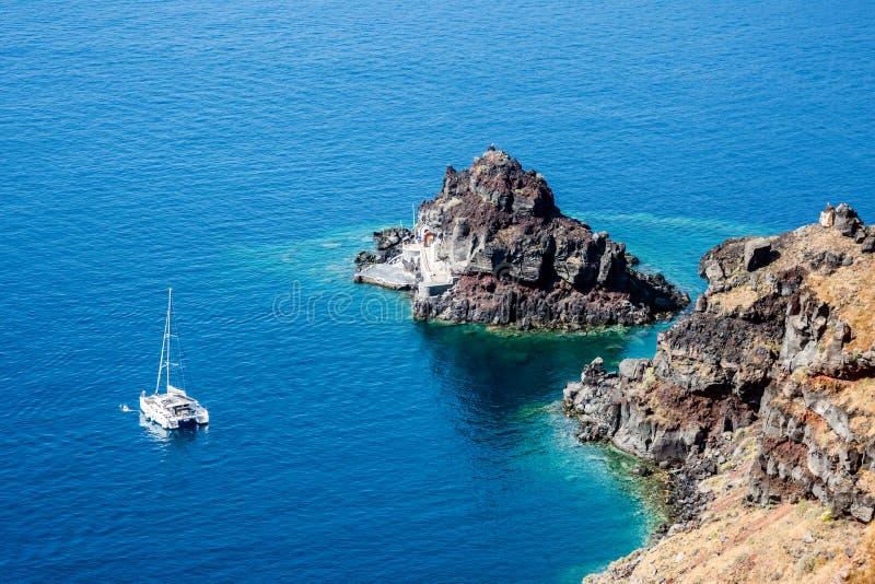 一艘停泊在希腊圣托里尼海岸的双体船 库存图片