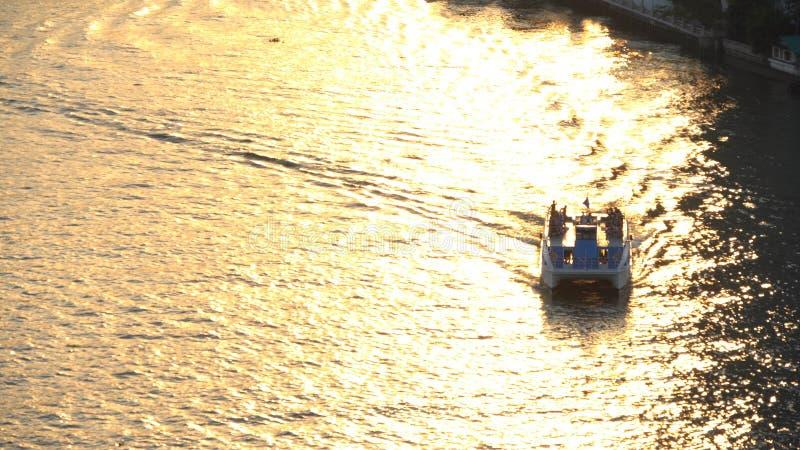 一艘巡航的小船或小船在昭拍耶河日落的在曼谷市,泰国 免版税库存照片