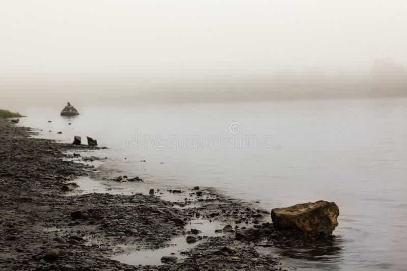 一艘橡皮艇的一个孤独的人在清早河, 库存图片