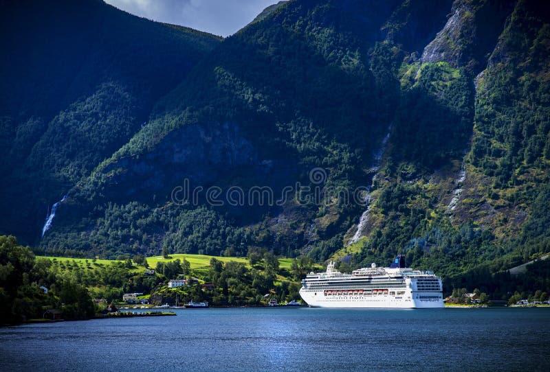 一艘白色明亮的巡航船海湾村庄抵达挪威 免版税库存照片