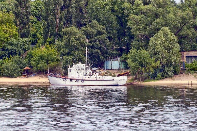 一艘白色船在河岸附近站立 免版税库存图片