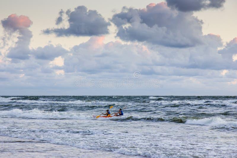 一艘皮船的人在波罗的海的日落 免版税库存图片