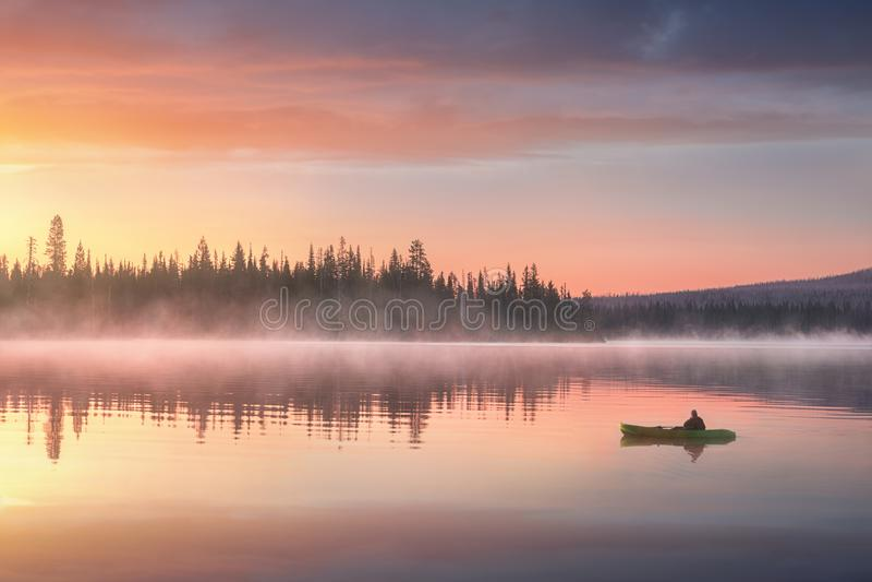 一艘皮船的人在风景日落的河 免版税库存图片