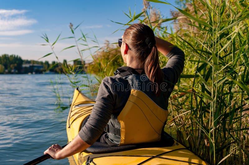 一艘皮船的女孩在河 库存照片