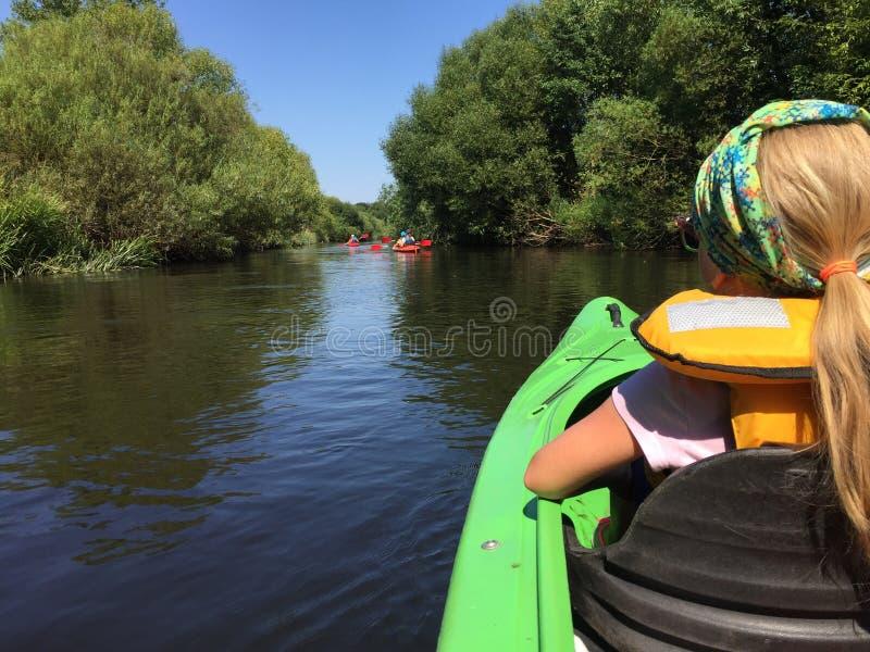 一艘皮船的女孩在Wieprza河,波兰 免版税库存图片