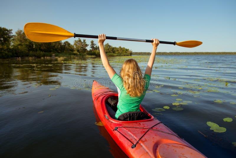 一艘皮船的妇女在有一支被上升的桨的一条河 免版税库存图片