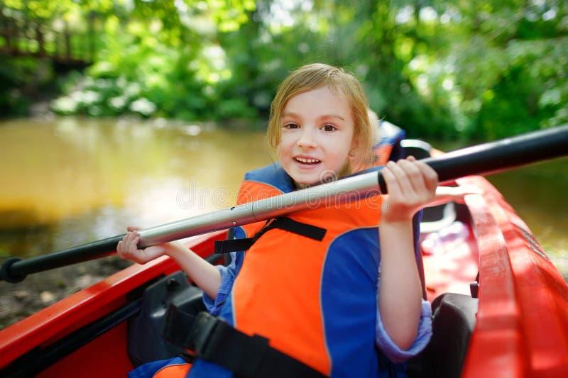一艘皮船的愉快的小女孩在河 免版税图库摄影