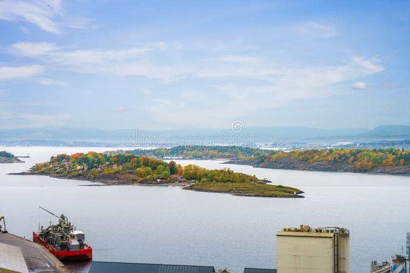 一艘红色船在奥斯陆海湾港口有秋天树的 库存图片