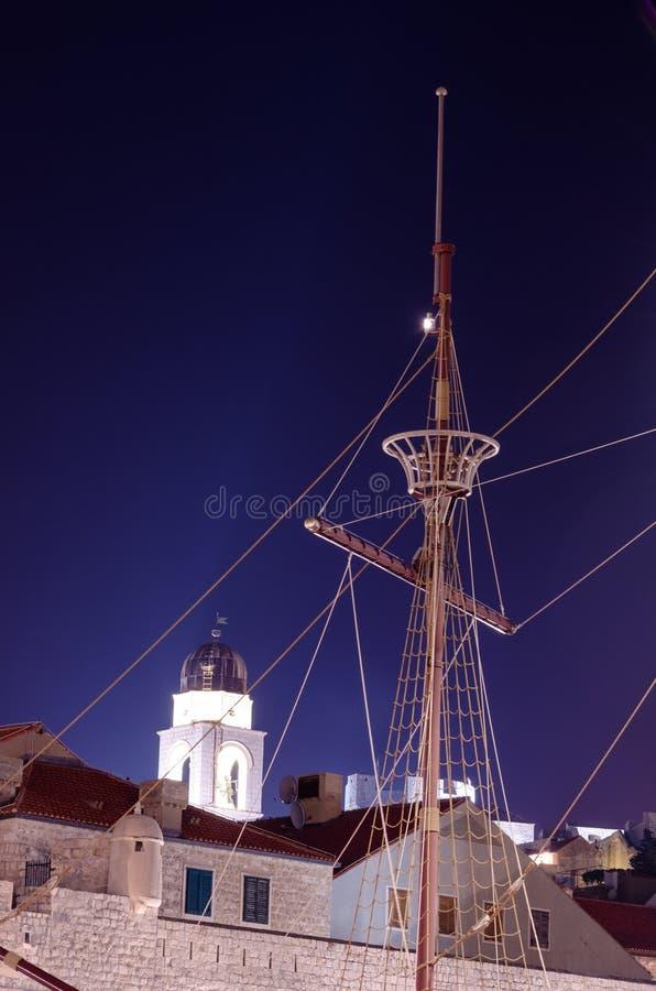 一艘老船的中桅和缆绳从发现时的反对一座清楚的钟楼在晚上 免版税图库摄影