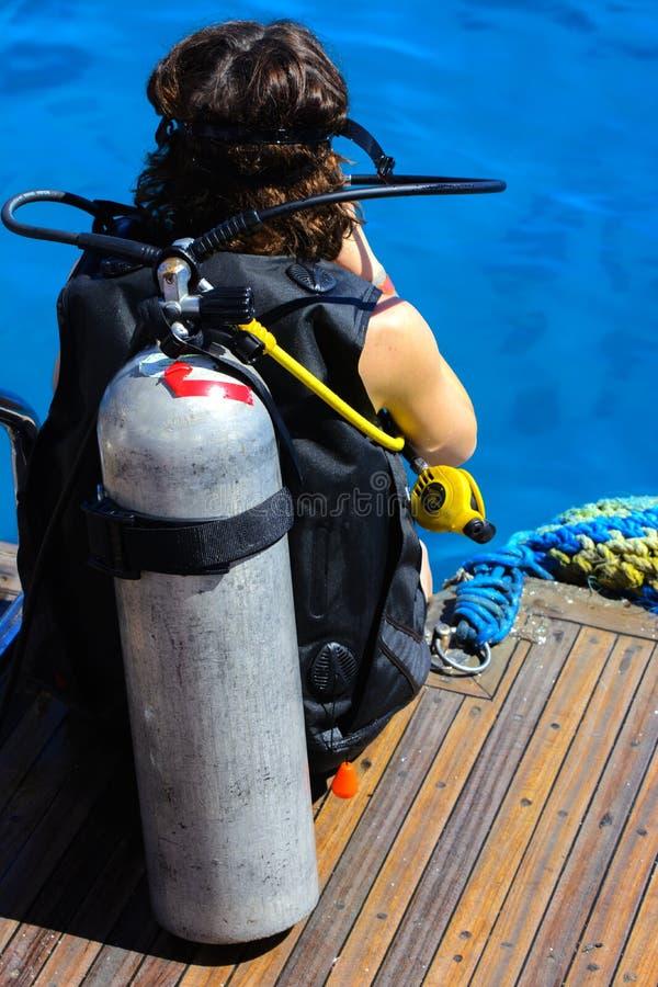 一艘船的船尾的一个女孩在潜水服的在透明和绿松石红海准备沉浸于 库存图片