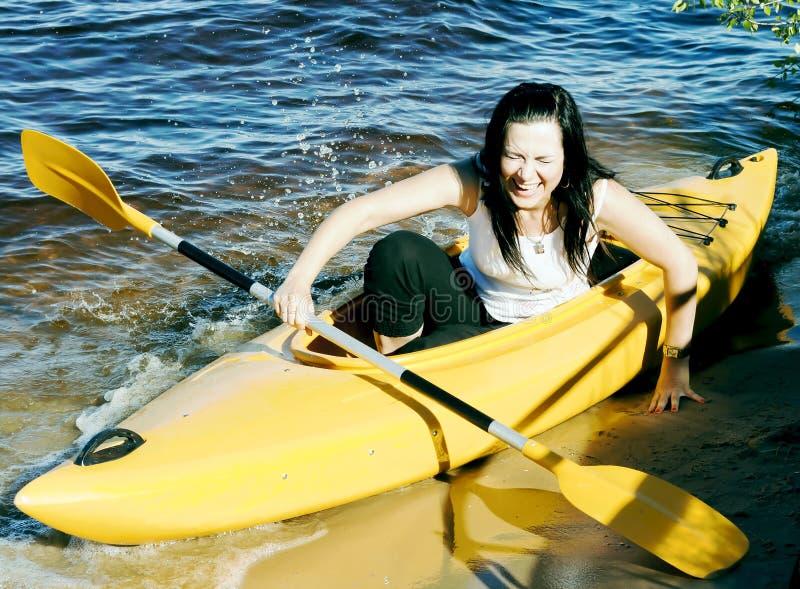 一艘黄色皮船的逗人喜爱的女孩 免版税库存图片