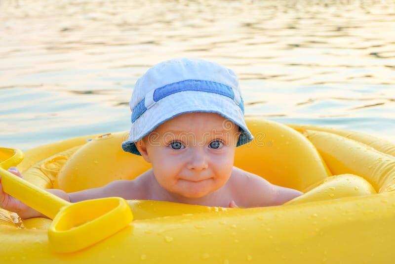 一艘黄色可膨胀的木筏的愉快的婴孩开阔水域表面上 免版税库存图片