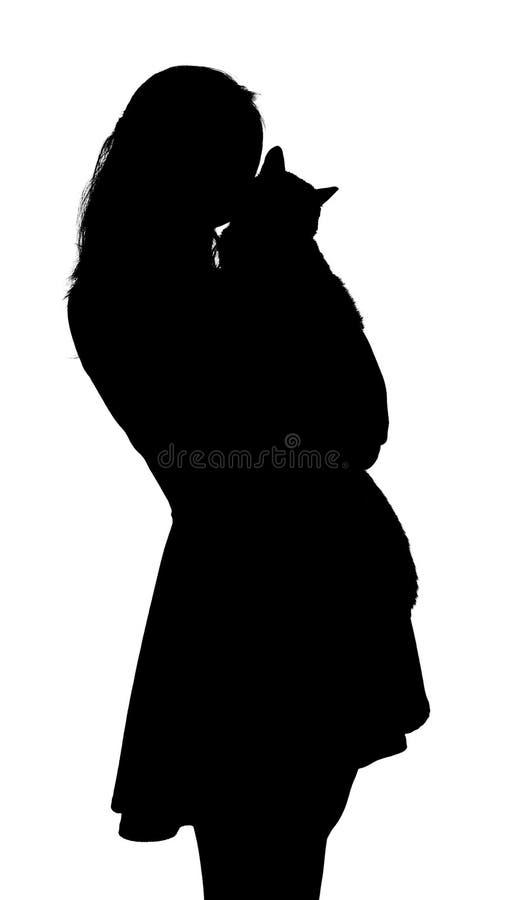 一苗条美女的剪影有一只猫的在她的胳膊,在白色被隔绝的背景的妇女的形象,宠物的概念, 库存照片