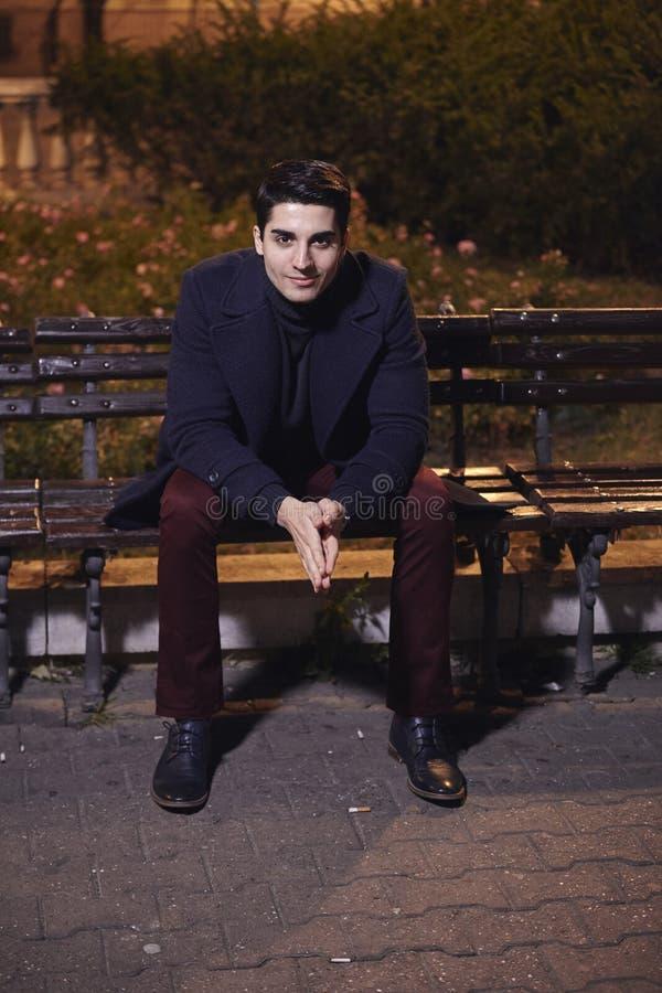 一英俊的年轻人,20-29岁,摆在,秋天衣裳,在城市广场的坐的长凳 夜间,黑暗 免版税库存图片