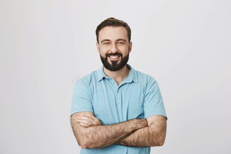 一英俊的有胡子的人微笑的看的画象对照相机用他的手在白色背景横渡了隔绝 免版税库存图片