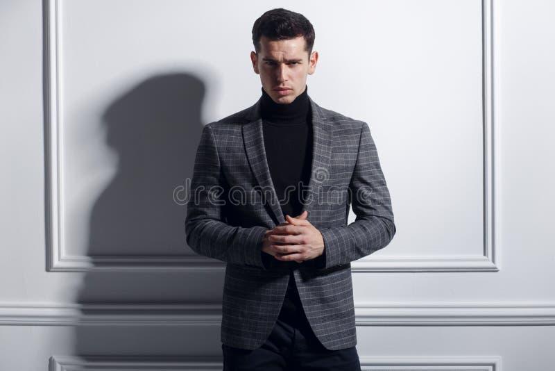 一英俊,典雅年轻人摆在的前面画象确信对时髦的黑灰色衣服在白色墙壁,演播室附近 免版税库存照片