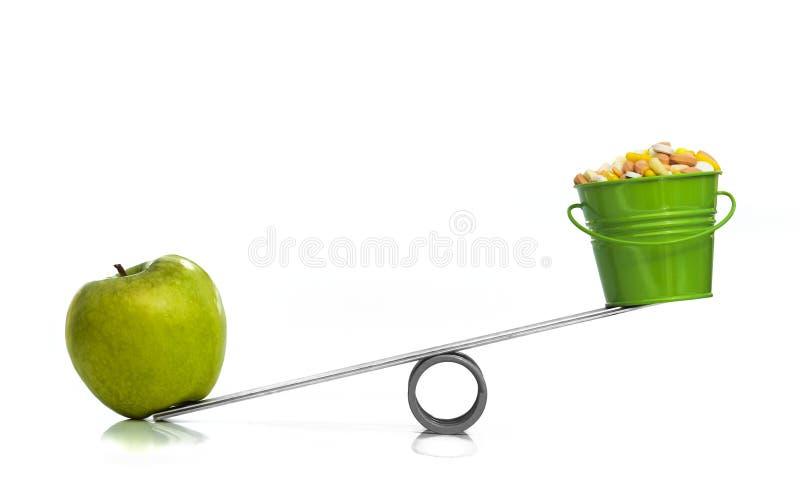 一苹果计算机对一个桶药片 免版税库存照片
