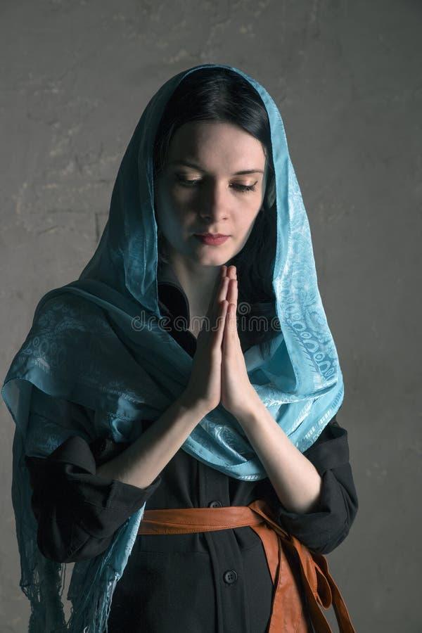 一蓝色披肩祈祷的美丽的少妇 库存图片