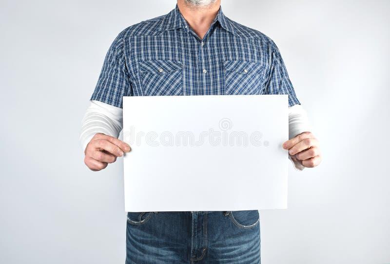 一蓝色格子衬衫和牛仔裤的人拿着空白长方形白皮书板料 免版税库存照片