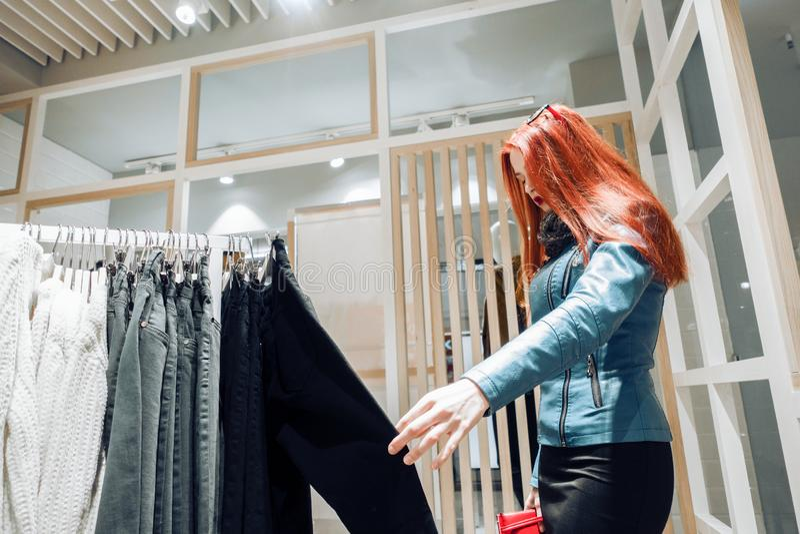 一蓝色皮夹克的红色头发少女选择裤子待售 图库摄影