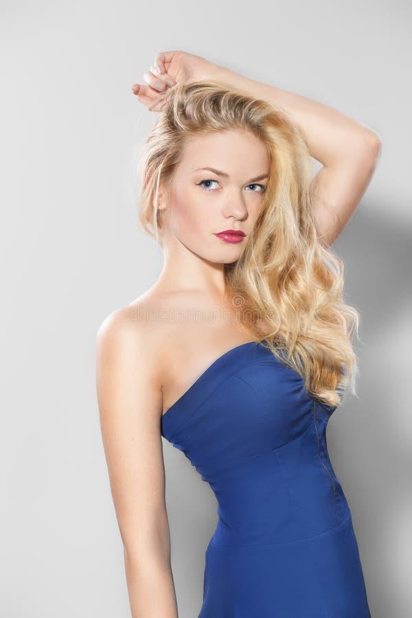 一蓝色礼服摆在的妇女 免版税图库摄影