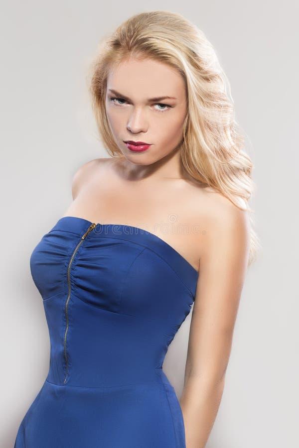 一蓝色礼服摆在的妇女 免版税库存图片