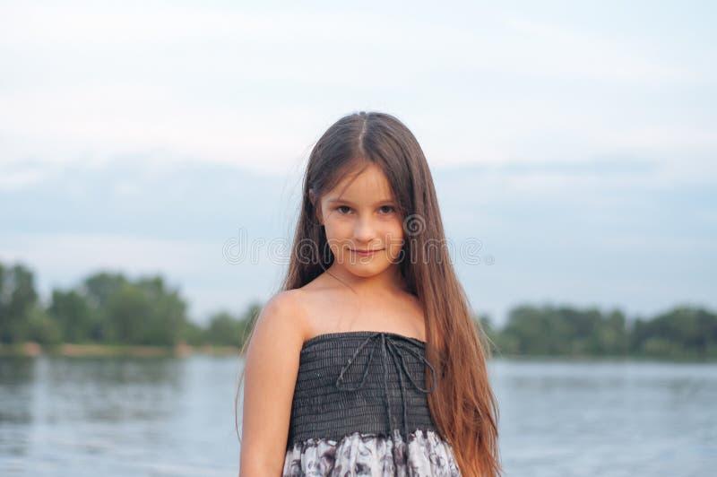 一被晒黑的女孩的画象的由海沙的sundress 免版税库存图片