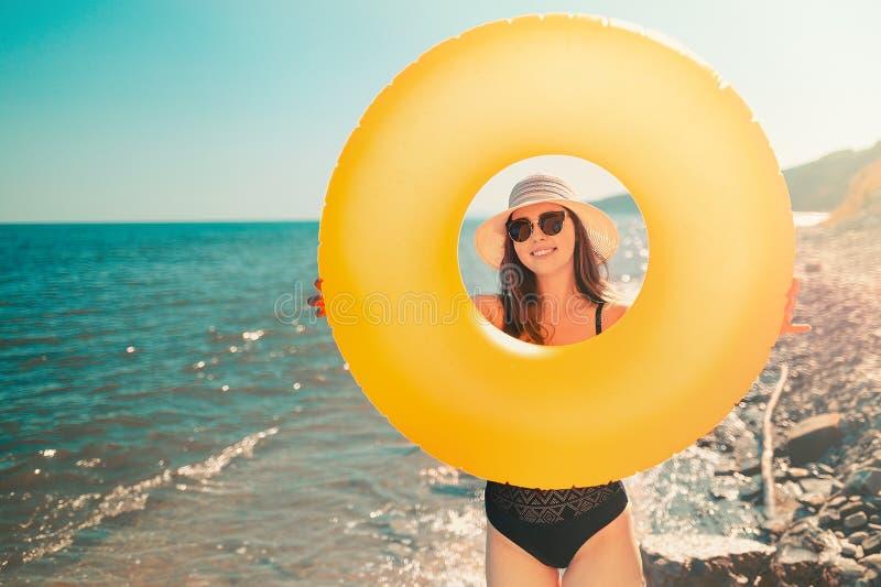 一被晒黑的年轻女人通过它举行橙色可膨胀的圈子和神色 在背景中是一个狂放的海滩 a的概念 库存图片