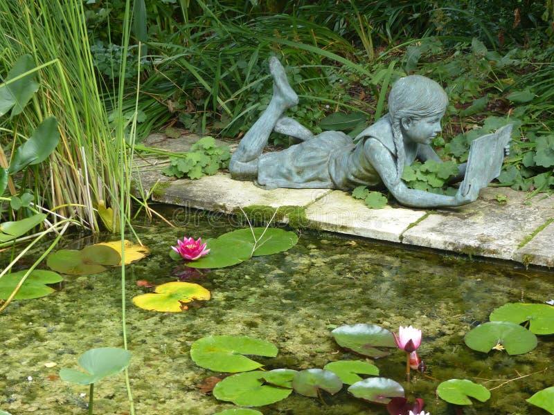 一读的少女的雕象在一个池塘附近的有荷花的 ?? 免版税库存照片