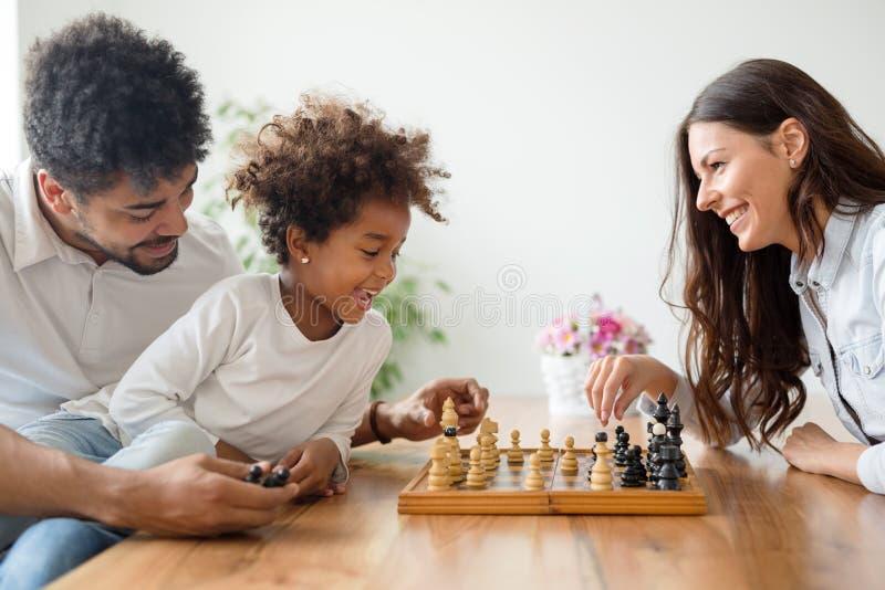一起下棋的愉快的家庭 免版税库存照片