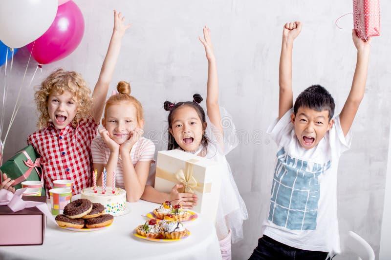 一起举手的愉快的小孩子在生日宴会 免版税库存图片