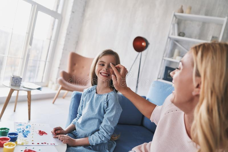 一起乐趣时间 照顾给她女儿面孔油漆和sm 免版税图库摄影