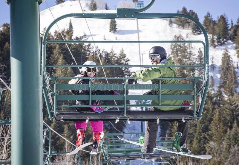 一起乘坐升降椅的父亲和女儿在滑雪胜地 图库摄影