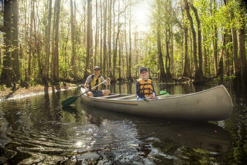 一起乘独木舟在一条热带河的父亲和儿子 库存照片
