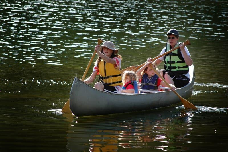 一起乘独木舟在湖的家庭在原野 免版税库存图片