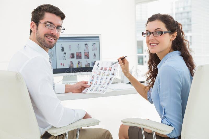 一起互动关于照片的微笑的同事 库存照片