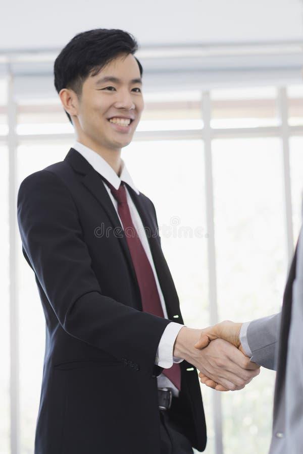 一起亚洲商人握手在办公室 免版税库存照片