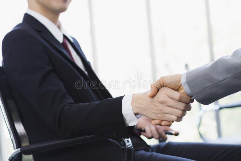 一起亚洲商人握手在办公室 免版税图库摄影
