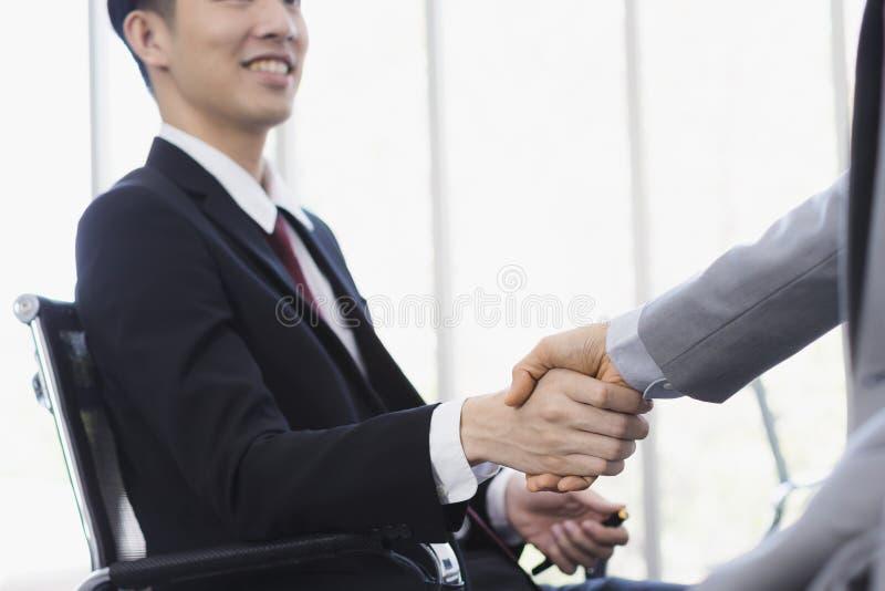 一起亚洲商人握手在办公室 图库摄影