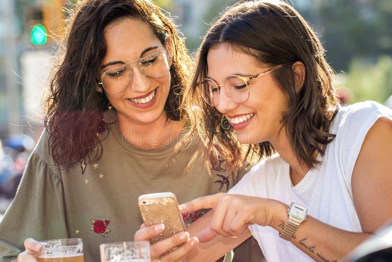 一起交往在智能手机的女友 免版税图库摄影