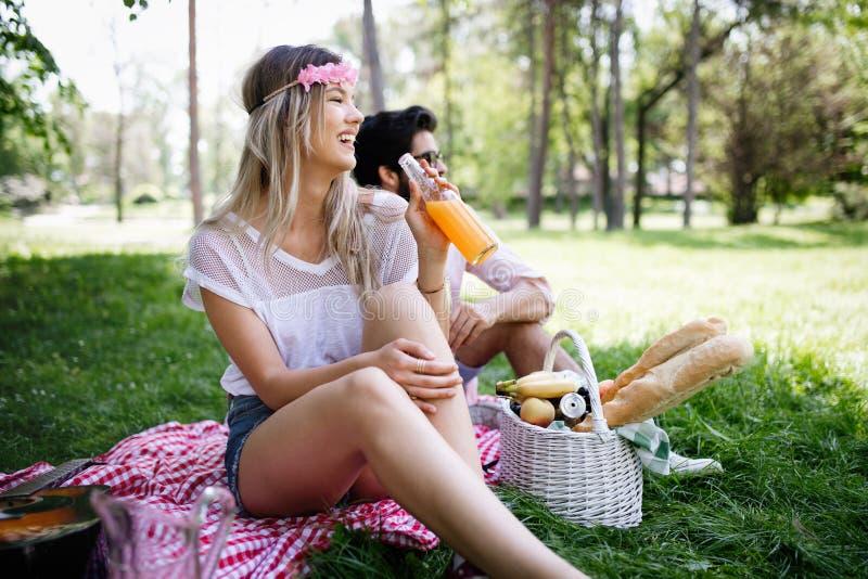 一起享受一顿野餐的愉快的年轻夫妇在公园 库存图片