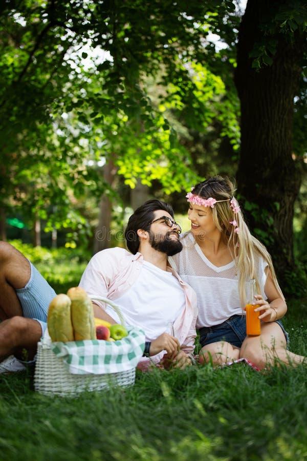 一起享受一顿野餐的愉快的年轻夫妇在公园 图库摄影