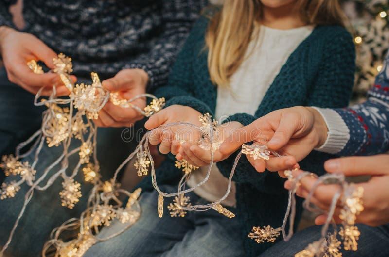 一起享受他们的假日时间的美丽的年轻家庭,装饰圣诞树,安排圣诞灯 免版税库存照片