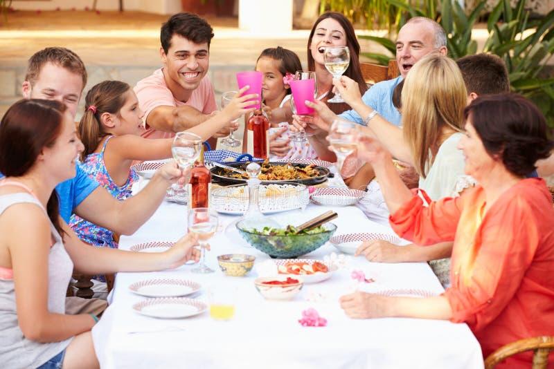 一起享受在大阳台的大家庭小组膳食 库存照片