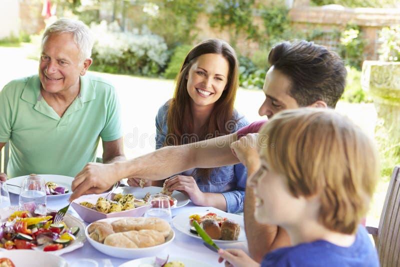 一起享受室外膳食的多一代家庭 库存照片