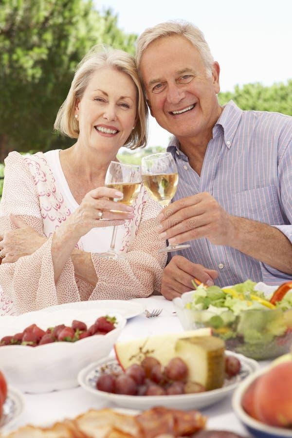 一起享受室外膳食的资深夫妇 免版税图库摄影