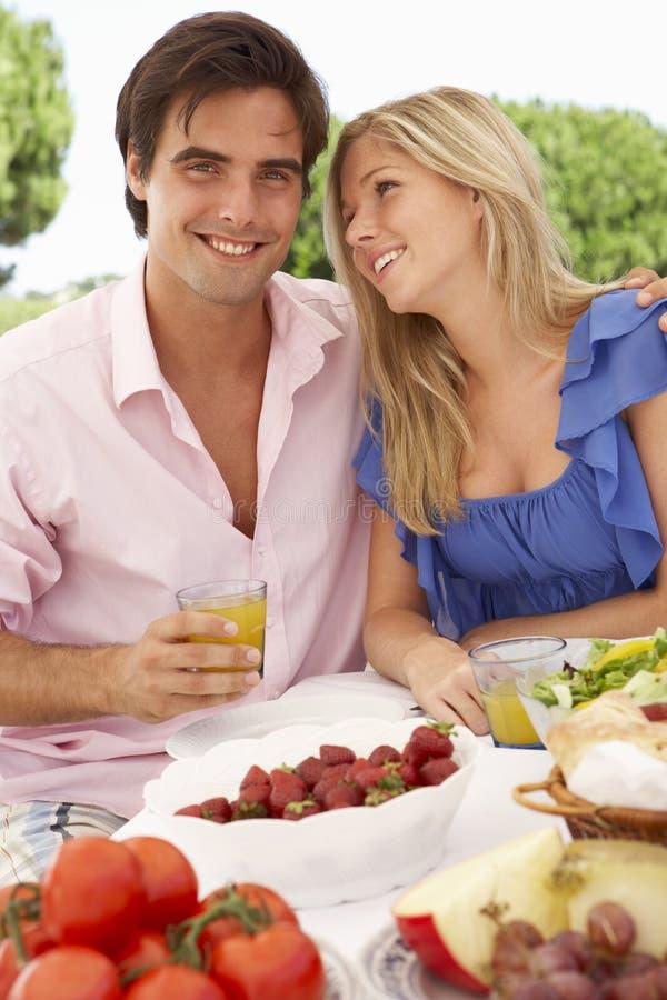 一起享受室外膳食的年轻夫妇 免版税库存照片