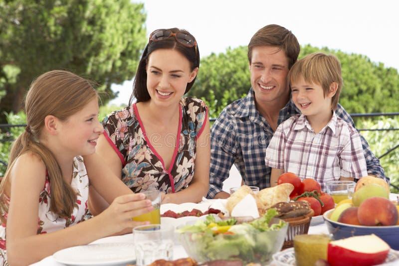 一起享受室外膳食的年轻家庭 免版税库存照片